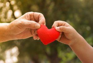 mano de adulto y mano de niño sosteniendo un corazón de fieltro