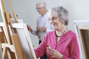 grupo de adultos en un taller de arte pintando sobre atriles