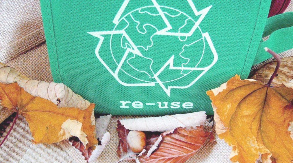 icono de re usar en una bolsa re utilizable y hojas otoñales