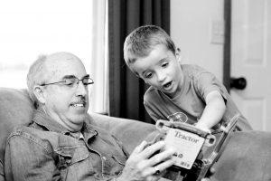 abuelo y nieto viendo un libro