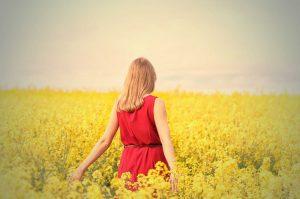 mujer de espaldas con vestido rojo en un campo de flores amarillas