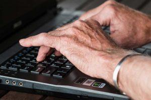 manos de hombre adulto sobre un teclado de notebook