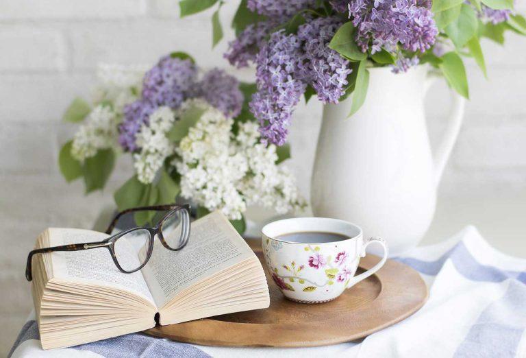 libro abierto, anteojos, taza de café y floreros con flores blanca y violetas
