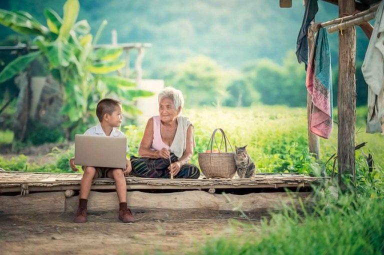 mujer anciana y niño con notebook, paisaje muy rústico