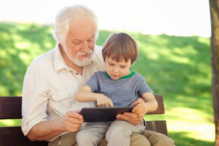 abuelo jugando con su nieto utilizando una tablet