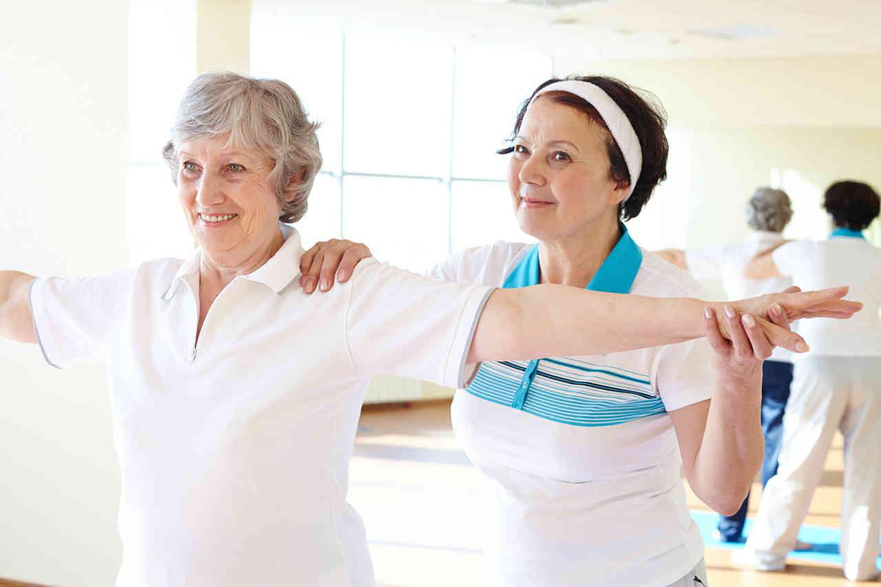 pareja de mujeres ayudándose en ejercicios físicos