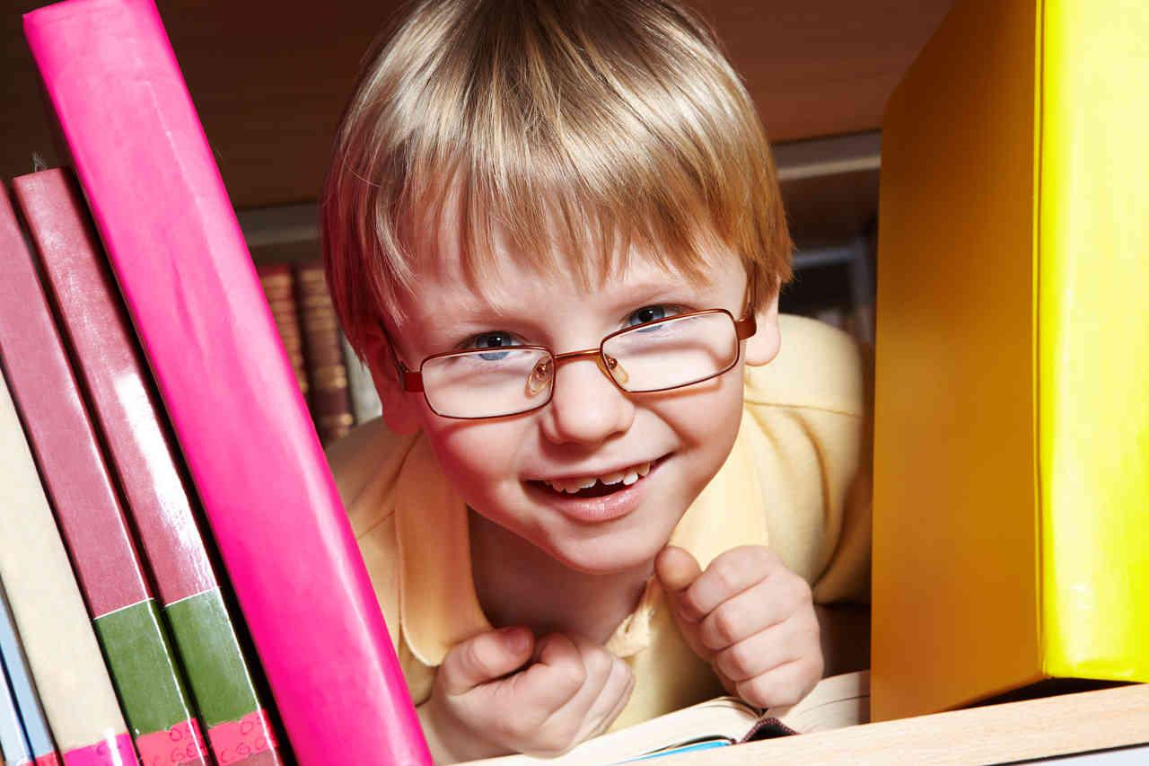 niño con anteojos asomado entre libros
