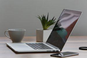 escritorio con notebook abierta, taza, celular y planta
