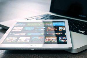 Tablet apoyada en una notebook con la pantalla de Netflix