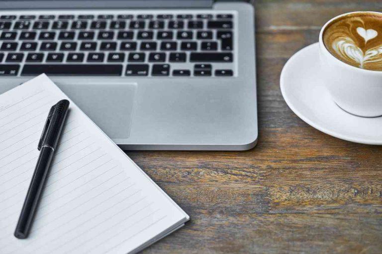 pc con cuaderno y café