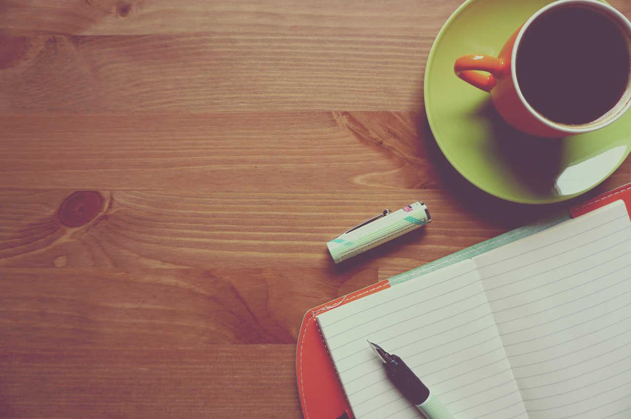 escritorio con cuaderno abierto y taza con café