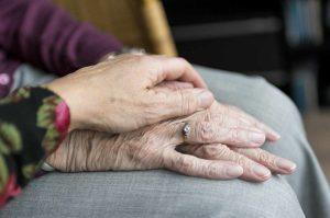 manos más jóvenes sobre manos más ancianas