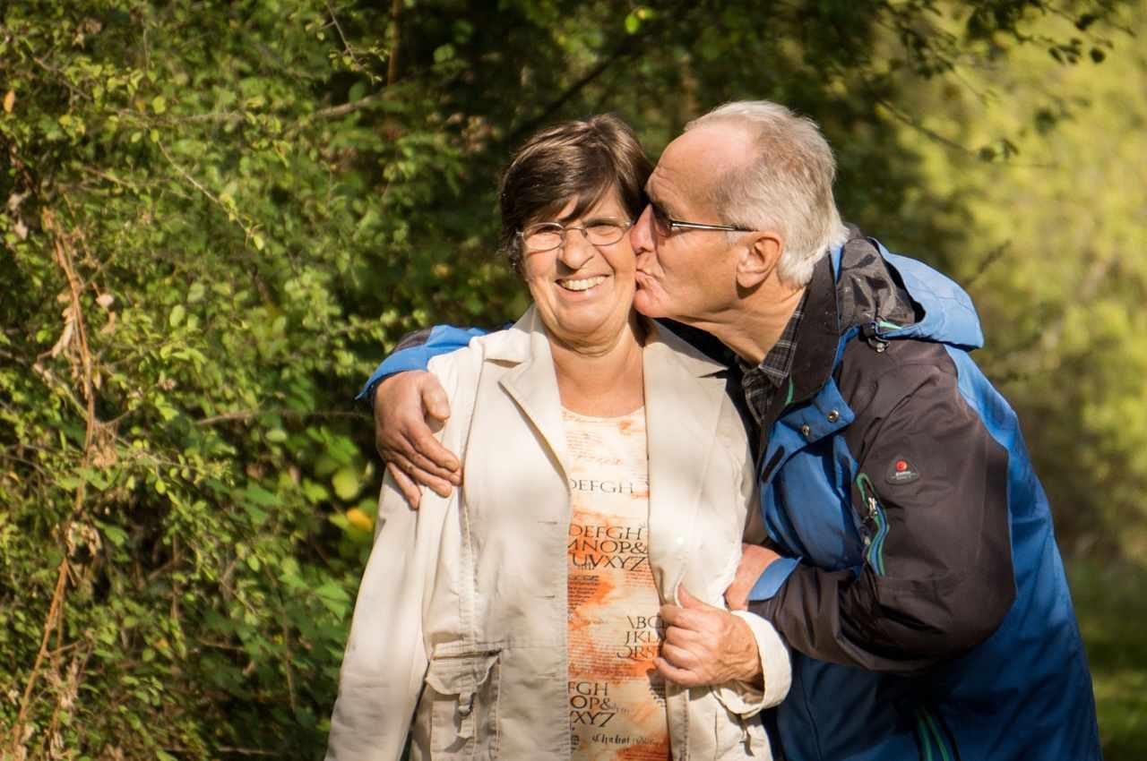 pareja mayor, el hombre abraza a la mujer y le da un beso en la mejilla