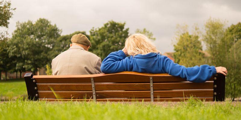 adultos sentados en un banco al aire libre disfrutando de buena salud