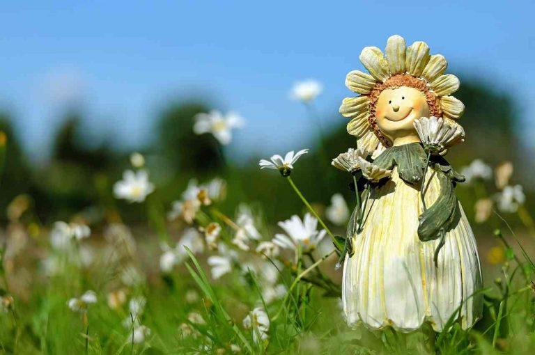 imágen de muñeca con forma de flor sonriendo en medio del campo muy motivada