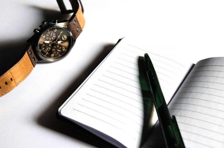 Reloj y libreta de anotaciones refiriendo a la jornada laboral en el Día Internacional del Trabajo