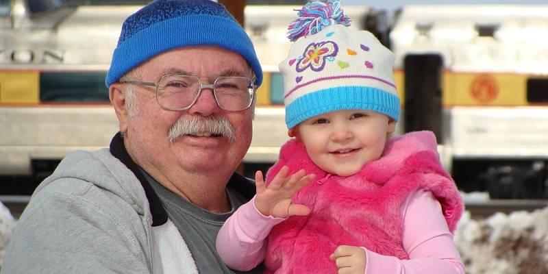 Abuelo con su nieta sonriendo en el día del nieto
