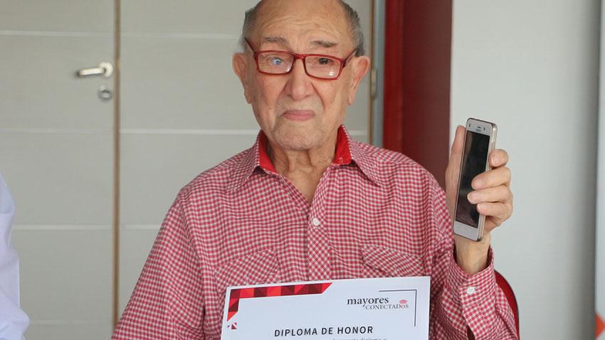 Martín Jacinto Aliz sostiene el celular Spanky Fácil, regalo de Mayores Conectados y el diploma de honor.