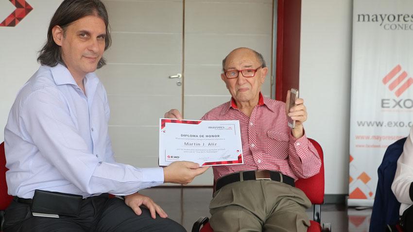 Martín Jacinto Aliz sostiene el celular Spanky Fácil, regalo de Mayores Conectados, junto a Jorge Scaramuzzo que le entrega el diploma de honor.